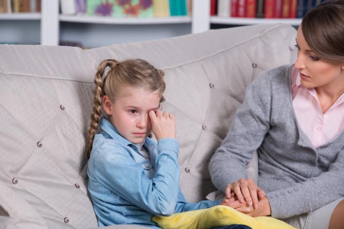 Девочка сидит на диване и плачет, мама её утешает