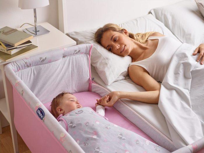 Детская кроватка стоит вплотную к родительской, мама держит малыша за ручку