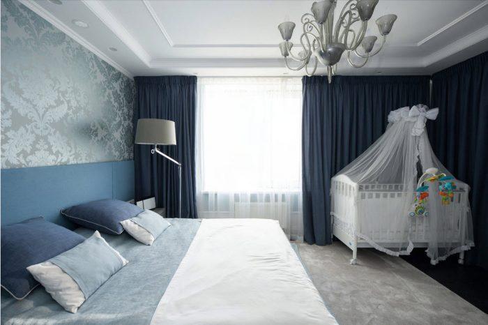 Супружеская постель, а в углу комнаты стоит детская кроватка