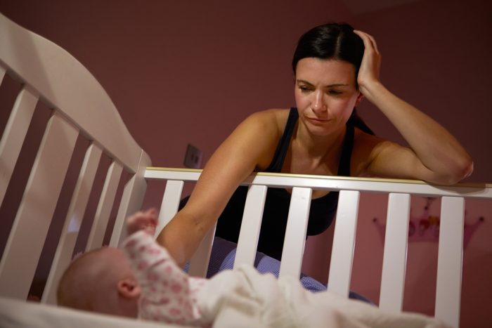 Мама стоит ночью у кроватки младенца