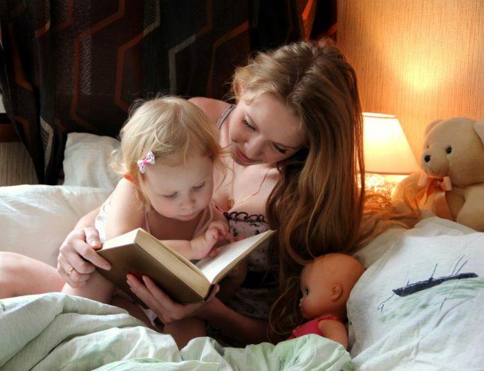 Мама читает маленькой дочке книжку перед сном, в детской постели находятся игрушки