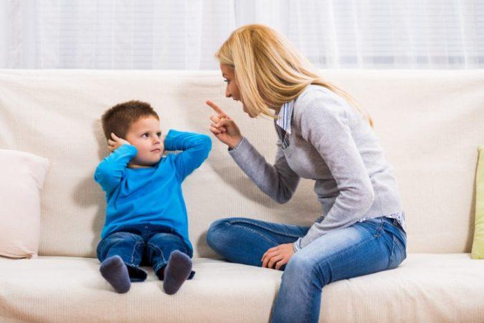 Мама ругает мальчика, грозит ему пальцем, а он закрывает уши