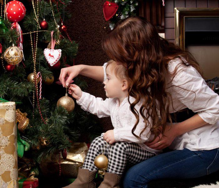 Мама наряжает ёлку с годовалым ребёнком