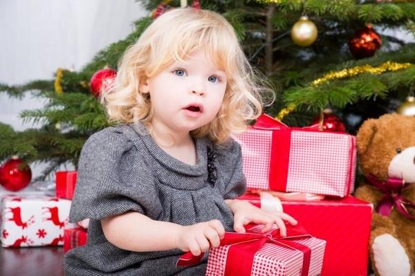 Годовалая девочка сидит возле ёлки и держит в руках подарок