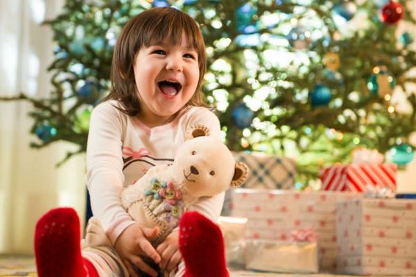Девочка держит в руках нового плюшевого мишку и радостно смеётся