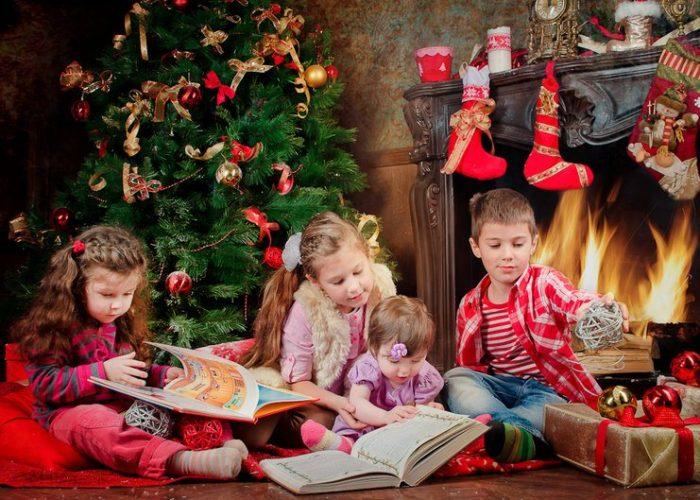 Дети сидят под ёлкой, рассматривают книжки и игрушки