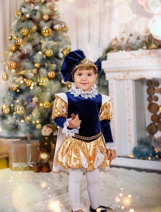 Двухлетний мальчик в костюме принца на фоне новогодней ёлочки