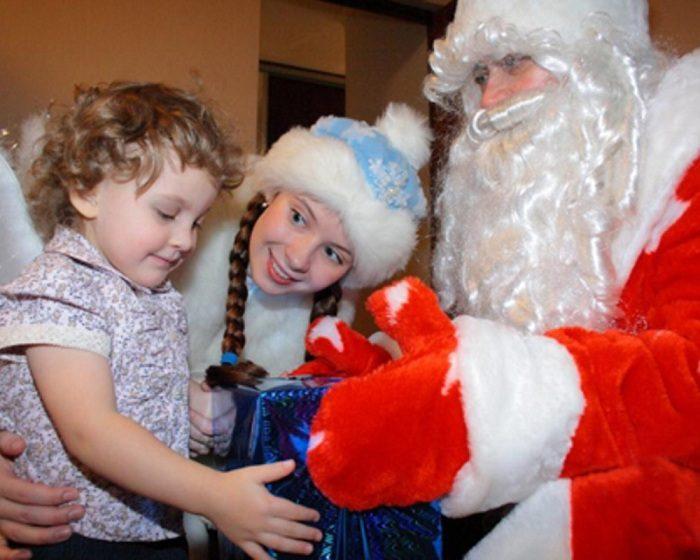 Дед Мороз со Снегурочкой вручают маленькой девочке подарок