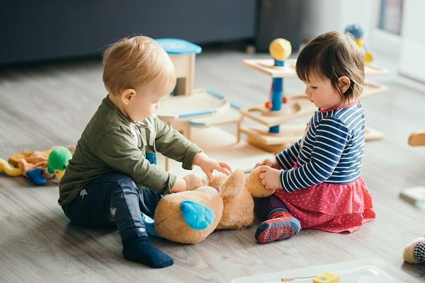 Двухлетние мальчик и девочка играют на полу