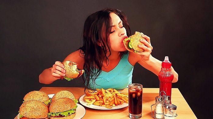 Девушка кусает сразу два гамбургера, на столе много другого фастфуда