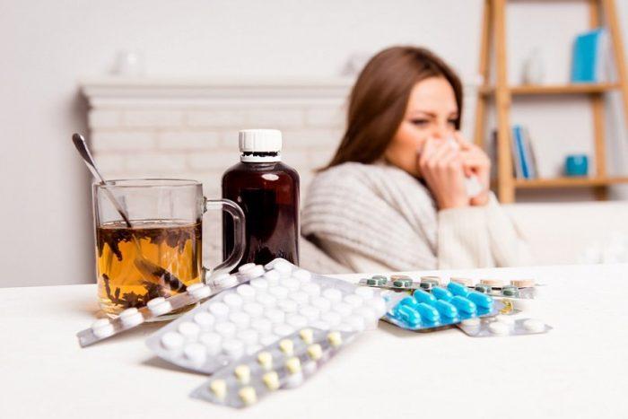 На столе лежат лекарства, на заднем плане простуженная девушка