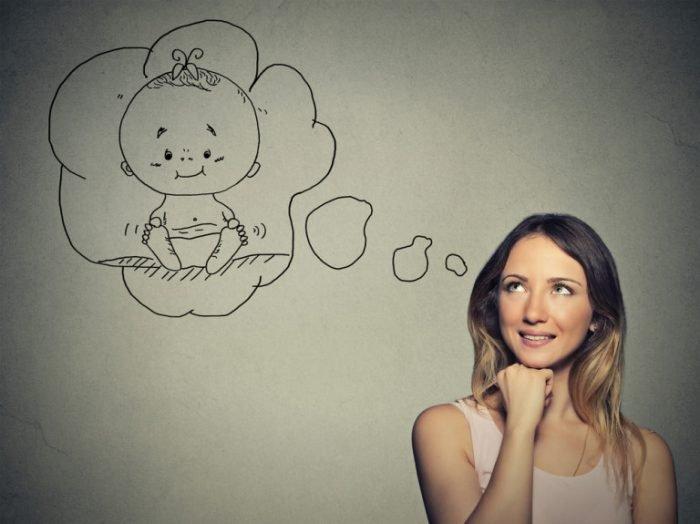 Женщина представляет себе ребёнка и улыбается