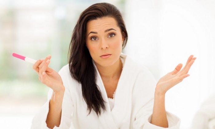 Женщина с тестом на беременность в руке