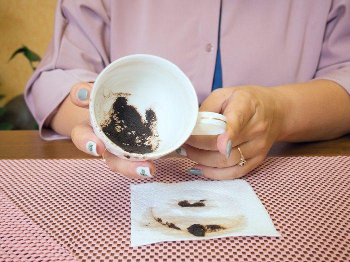 Женщина держит в руках чашку с кофейной гущей