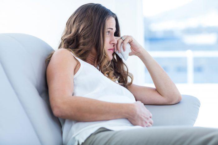 Беременная сидит на диване и плачет