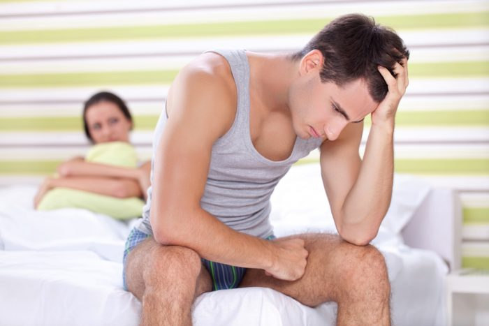 Мужчина грустит, сидя на кровати