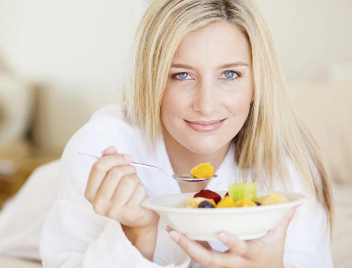 девушка держит тарелку с фруктовым салатом