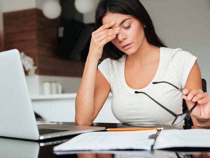 девушка, сидя перед ноутбуком и сняв очки, держится за переносицу