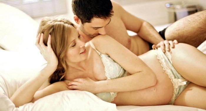 Беременная женщина с мужем в постели
