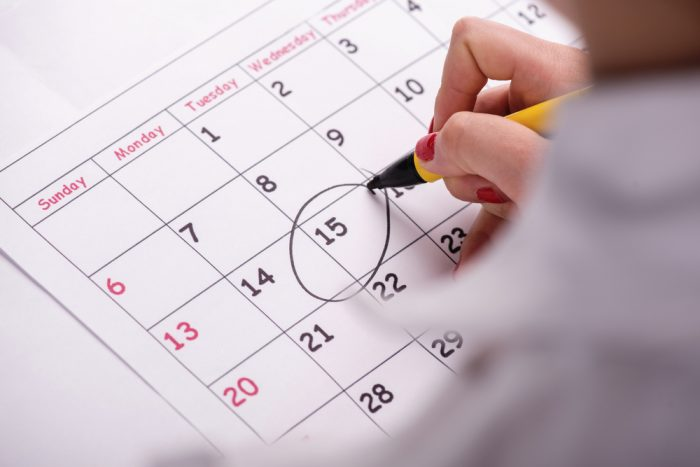 Женщина делает отметку в календаре