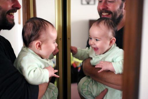 Папа с грудным ребёнком смотрятся в зеркало и улыбаются своему отражению