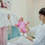 Медсестра держит ребёнка