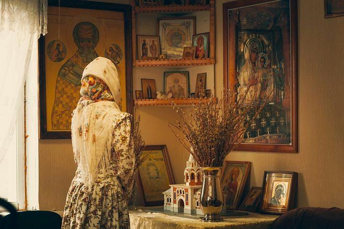 Женщина молится перед домашним иконостасом