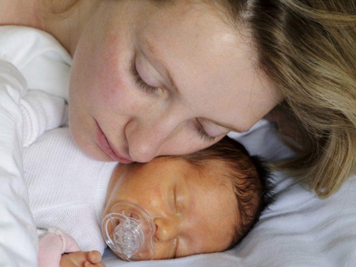 мама прислонилась щекой к младенцу, у которого желтуха