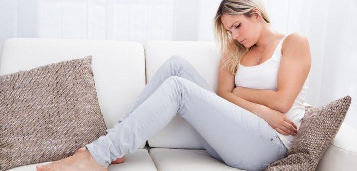 Женщина сидит на диване обхватив живот руками