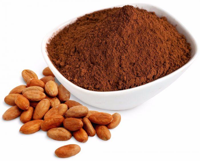 Какао-порошок в пиалке, рядом бобы