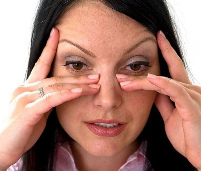 женщина приложила пальцы к боковым поверхностям носа
