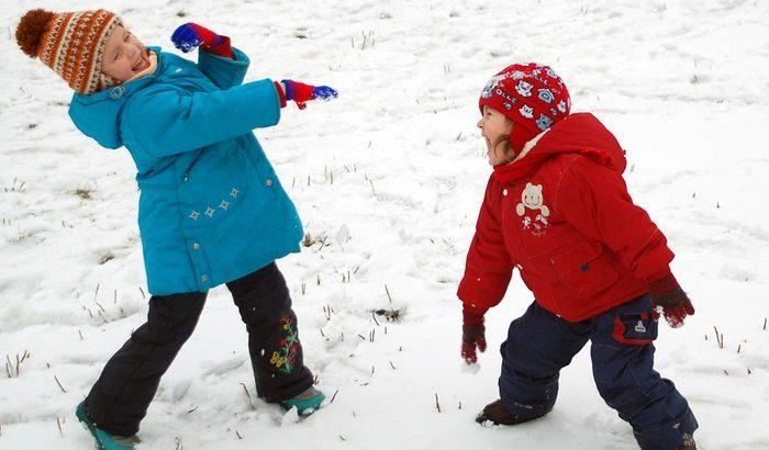 Девочки играют в снежки на прогулке