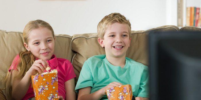Дети едят попкорн, смотрят телевизор и улыбаются