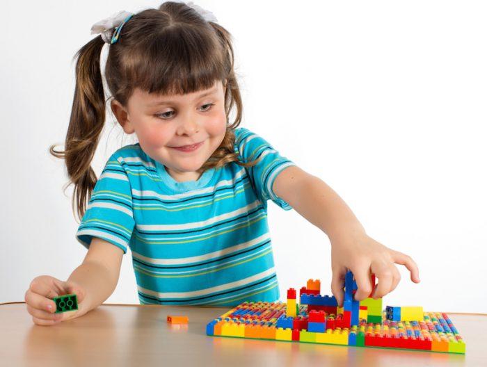 девочка собирает детали из конструктора Лего