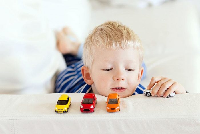 мальчик лёжа играет с машинками