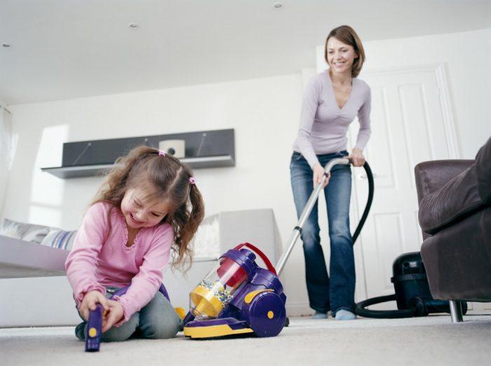девочка чистит ковёр пылесосом