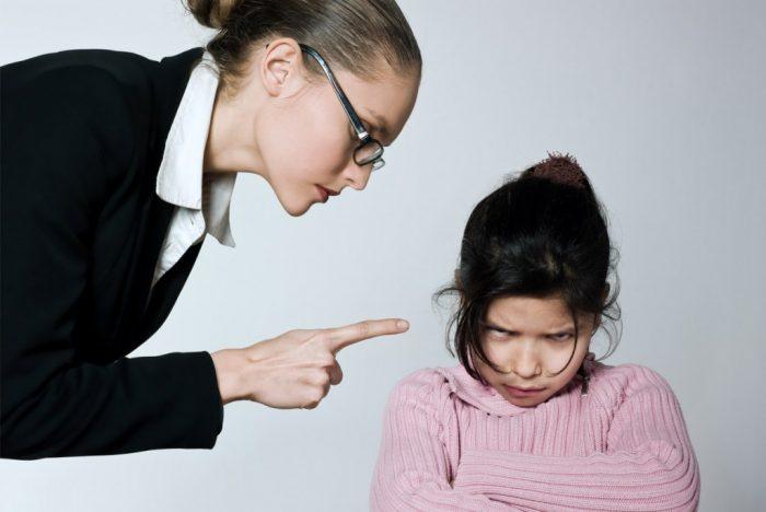 женщина, склонившись над девочкой, тычет в неё пальцем