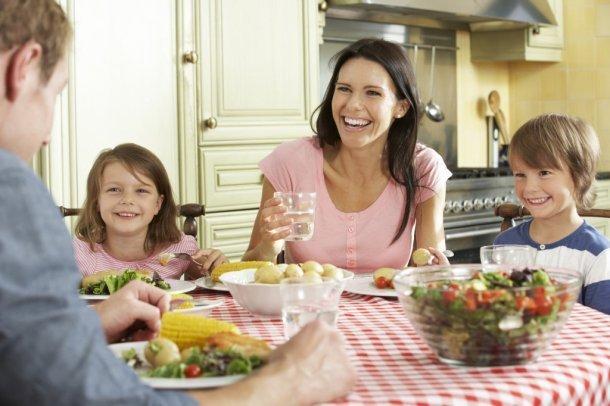 родители, сын и дочь сидят за накрытым столом