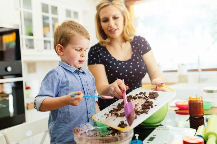Мальчик вместе с мамой готовит на кухне