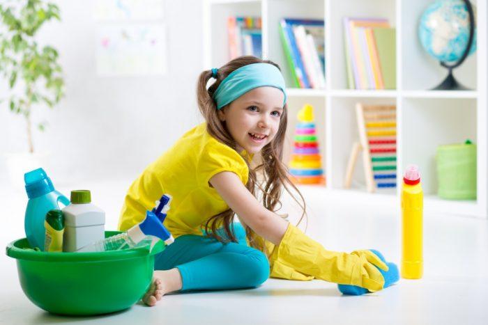 Девочка в перчатках убирает в комнате