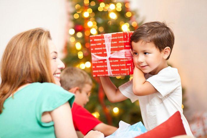 ребёнок держит коробку, перевязанную лентой, рядом улыбается мама
