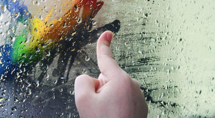 Палец, рисующий на стекле