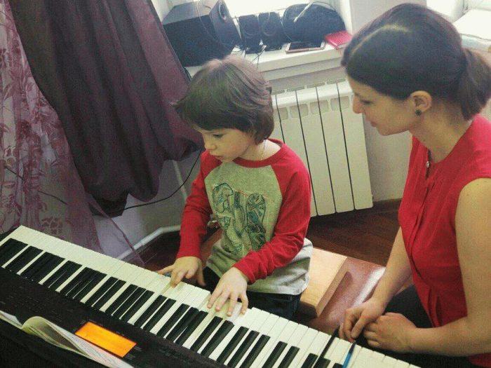 ребёнок играет на фортепиано, рядом сидит учительница