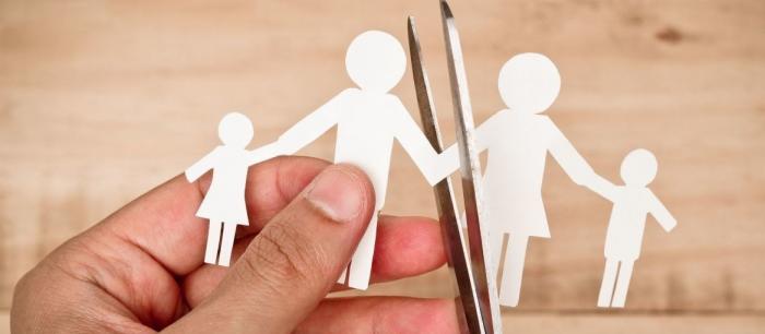Человек разрезает фигурки семьи