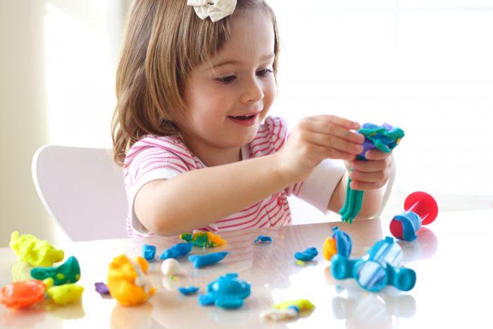 Радостная девочка играет в пластилин
