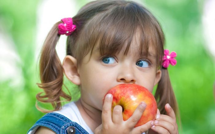 девочка поднесла ко рту яблоко