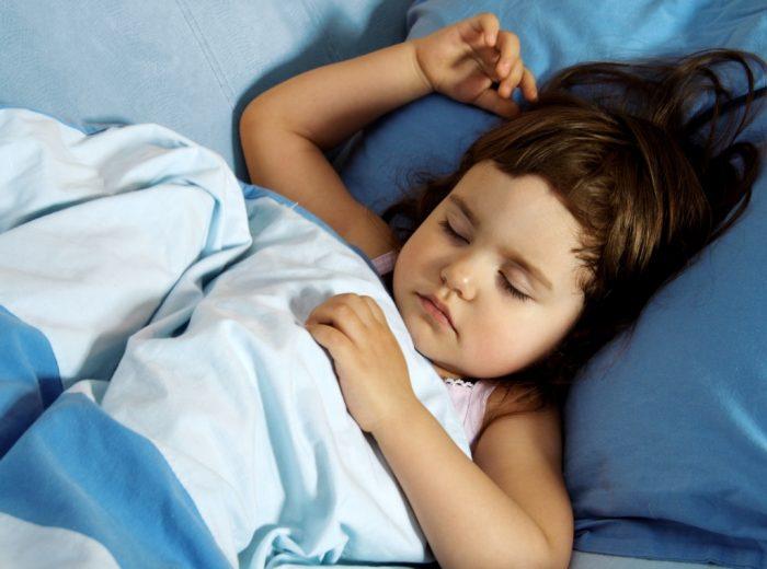 ребёнок лежит в кровати, закрыв глаза