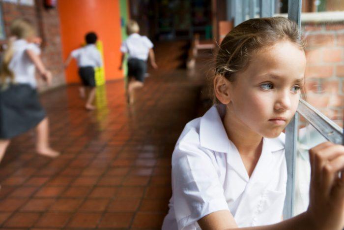 Худенькая девочка грустно смотрит в окно