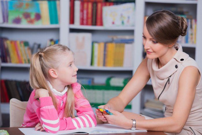 Женщина психолог беседует с девочкой