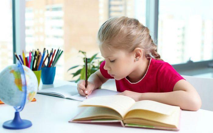 девочка пишет в тетради, рядом глобус
